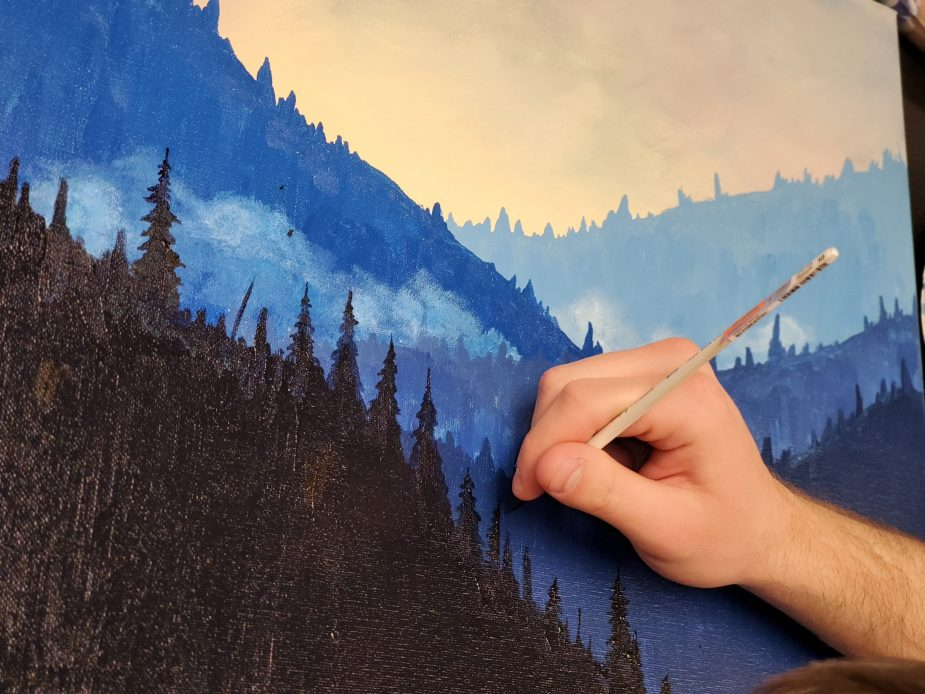 a hand working on a painting