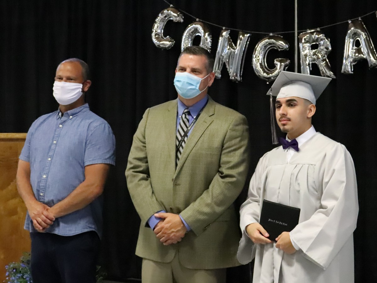 student in cap and gown with superintendent and facilities assistant director