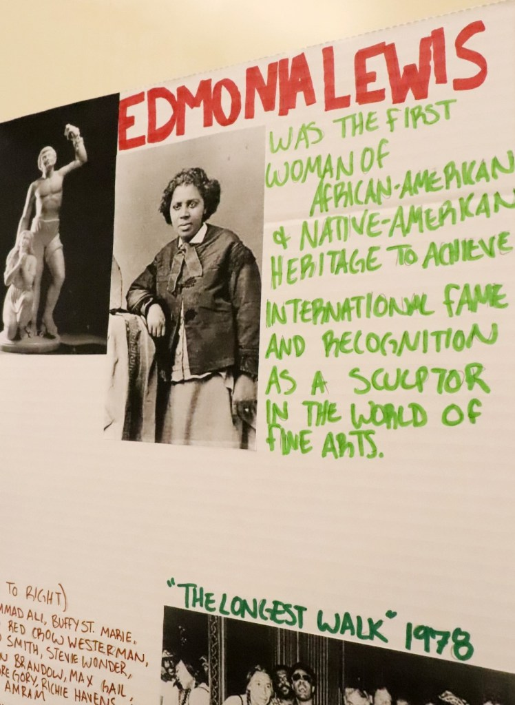 """A close-up of a display board with a photo and text that says, """"Edmona Lewis was the first woman of African-American and Native-American heritage to achieve international fame and recognition as a sculptor in the world of fine arts."""""""