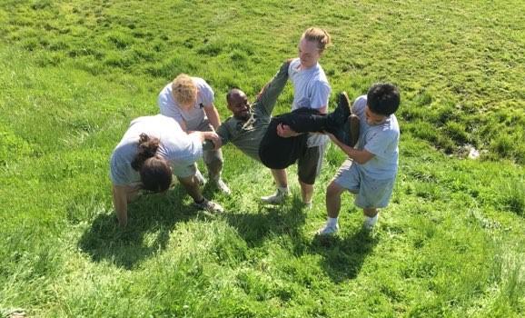 four teen boys carry another boy across a grassy field