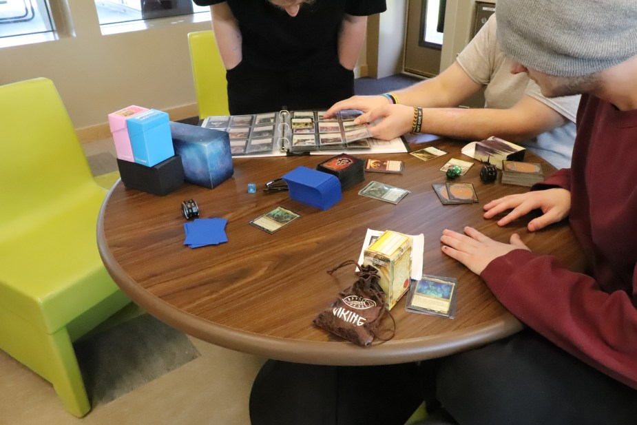 several young people play card game at a table