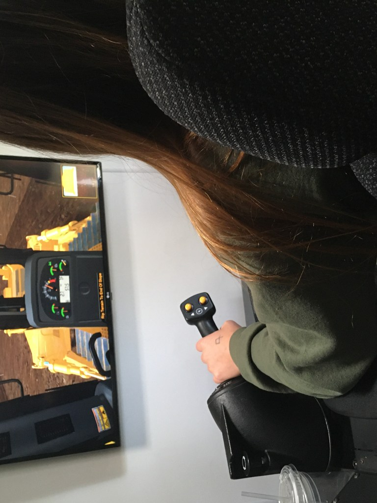 a young woman sits in front of a screen and uses a joystick