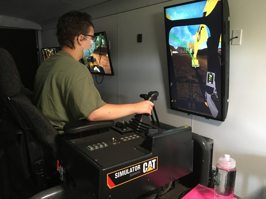 a young man sits in front of a screen and uses a joystick