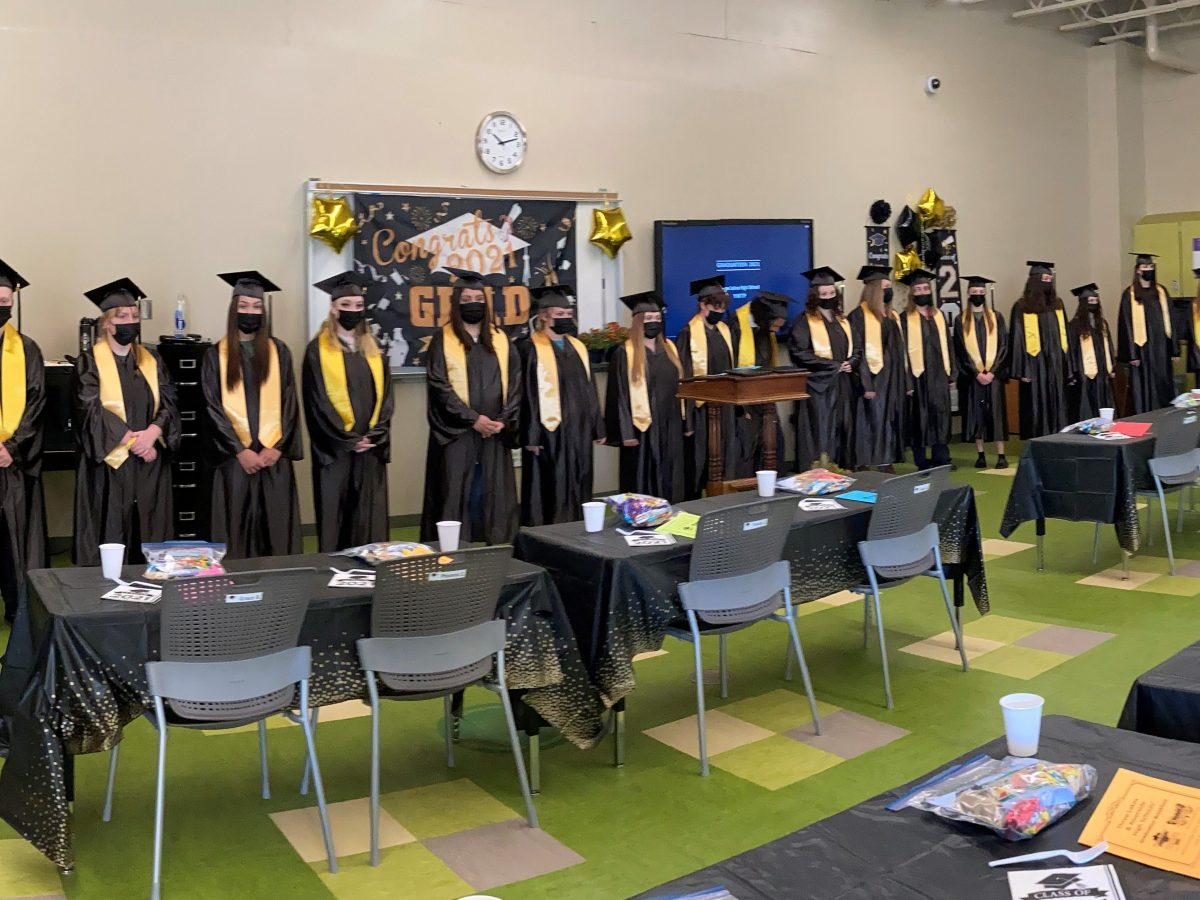 group of graduates in caps and gowns standing at front of room