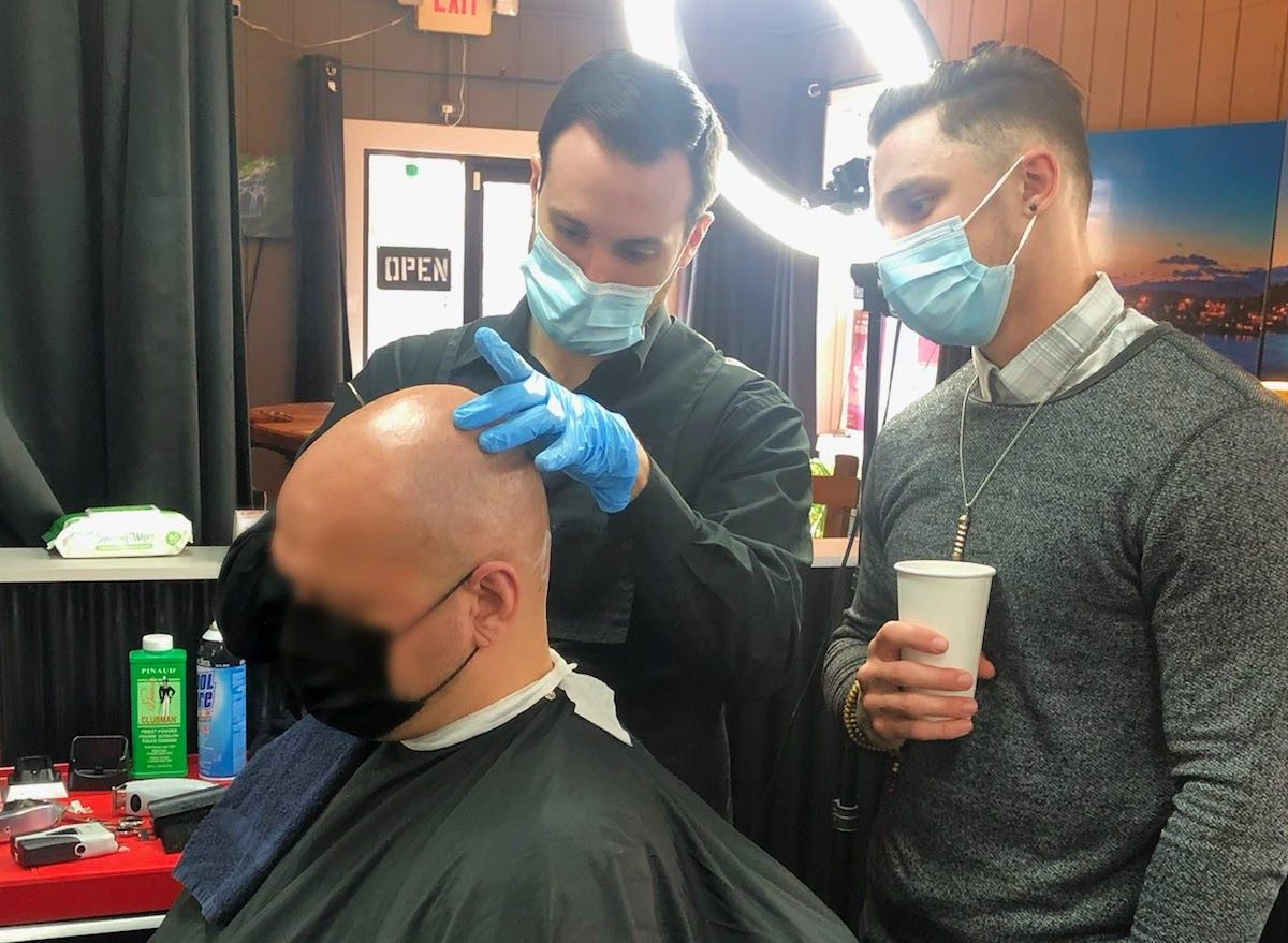 Two young men in a barbershop shave an older man's head