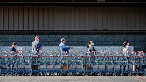 Five people waiting outside a supermarket, standing far apart.