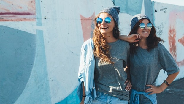Image of two young women against a painted wall.