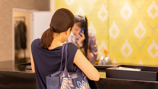 Image of woman at checkout in clothing store with staff on the phone enquiry.