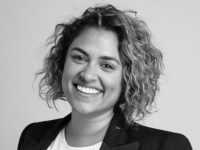 A black and white shot of Charlene Perera with short curly hair and a black blazer