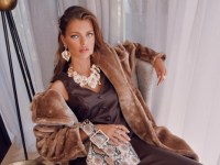 Girl with long hair and lots of jewellery on a chair with a faux fur coat.