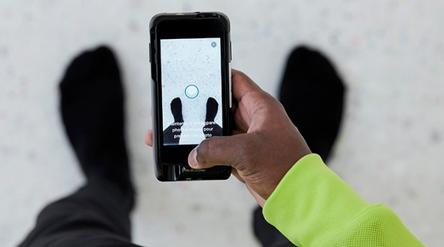 A customer holding a mobile phone with the Nike app open.