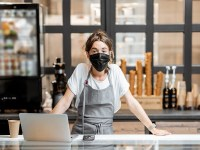 Image of a woman wearing a face mask at a cafe