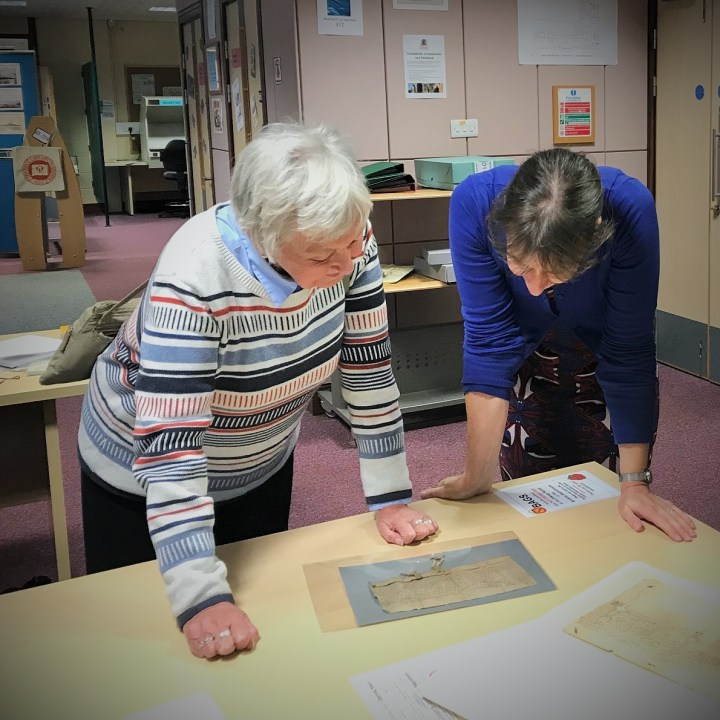 Jennifer and Sheena, the owner of this 1402 disposition, look at the document at Orkney Library