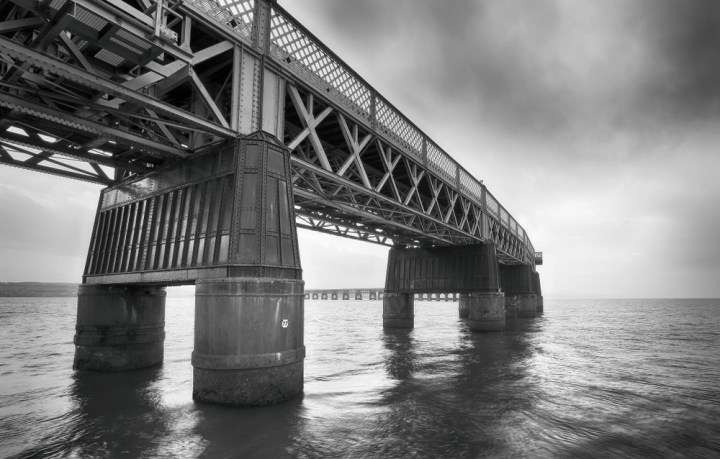 Tay Rail Bridge in evening light crosses the River Firth of Tay, textured in black and white tones with dark sky