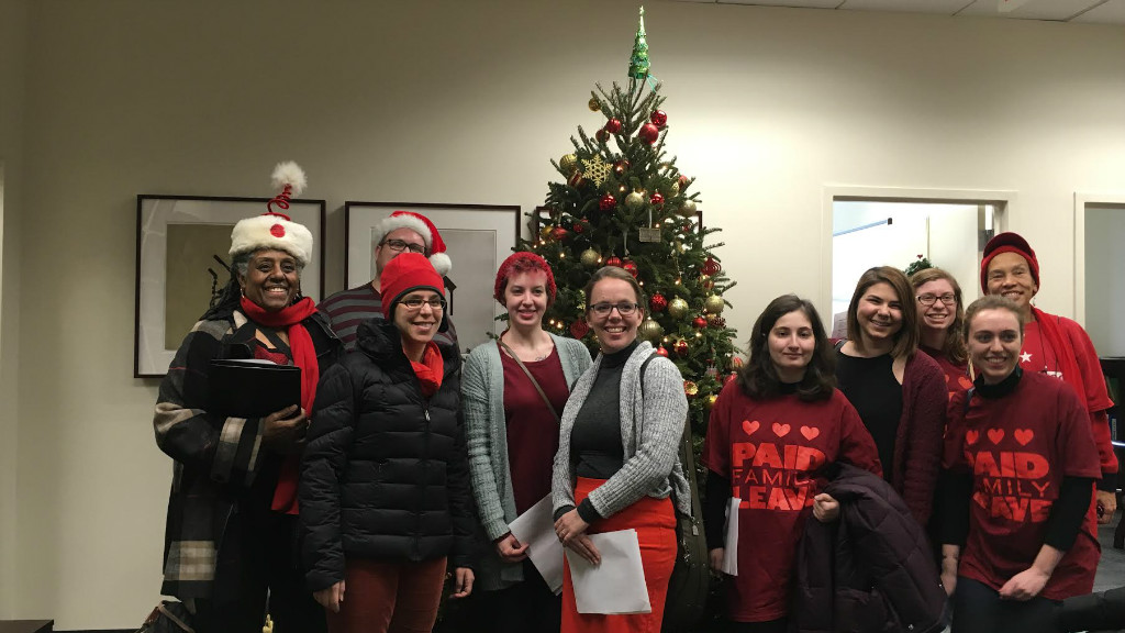 """Ten Christmas Carolers in an office posing smiled in front of a Christmas Tree. All are wearing festive attire, a few are wearing t-shirts that say """"DC Paid Family Leave""""."""