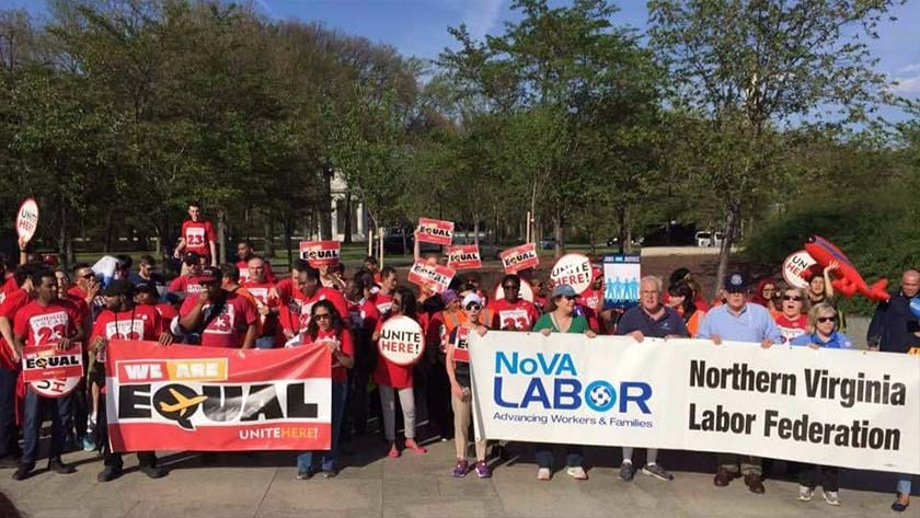 """People from a labor march, mostly in red t-shirts, stand with the DC WWI Memorial behind them. There are two banners in front. On the left, it says """"We are Equal"""", and on the right it says """"NoVA Labor"""". Most people are holding small signs saying """"We are Equal"""" or """"Unite Here""""."""