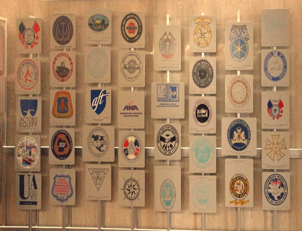The US Department of Labor Century of Service Honor Roll of American Labor Organizations in the lobby of the Francis Perkins Building. Marble wall with the seals of every pertinent labor union.