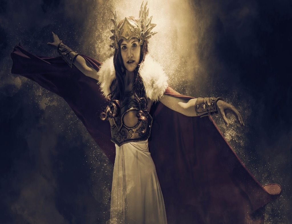 Brünnhilde wearing the fabled helmet, breastplate, spiked bracelets, wolfskin, and white skirt, and red cape. Her arms are both extended to to the sides but bent at the elbows. Her right hand is extended and left hand his limp. There is a glow behind her.