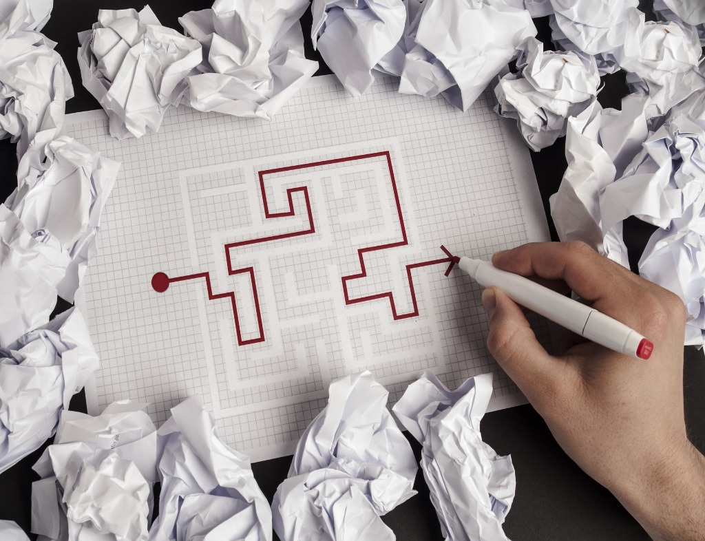 A completed maze. Gray backdrop, white lines, and a red line that goes from a point on the left to an arrowhead on the right. A hand holds a pen over the arrowhead. Crumpled white pieces of paper surround the maze.