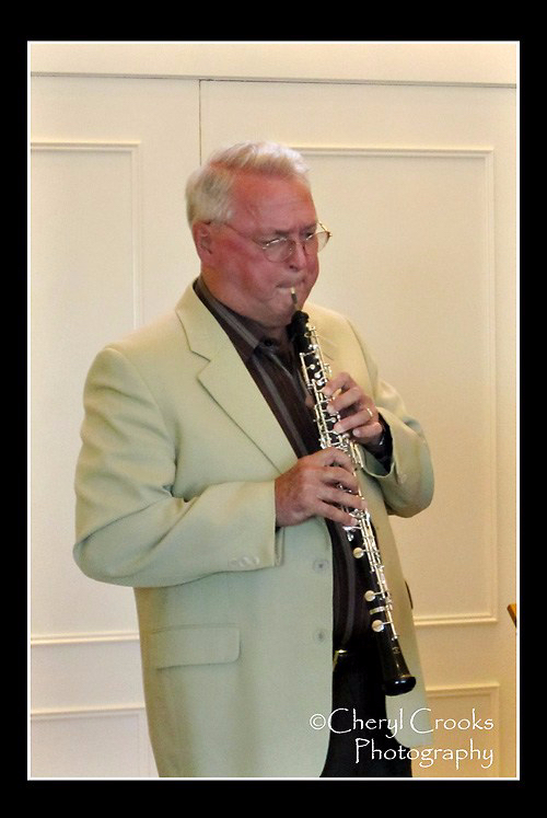 Joe Robinson in a white dinner jacket playing the oboe