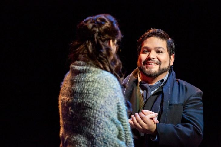 Ernesto Ramirez in character for La Boheme holding hand of soprano