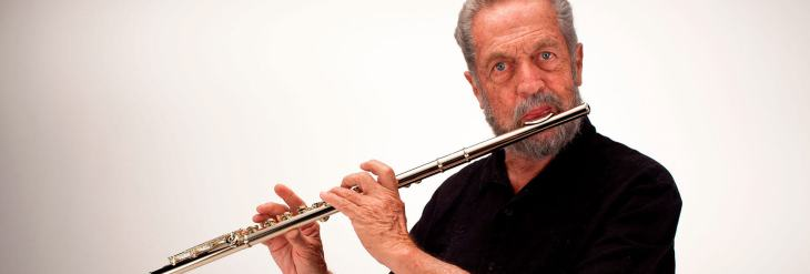 promo shot of Sheridon Stokes playing his flute in front of a white background