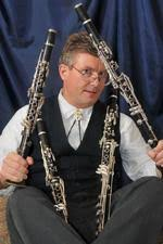 Kenneth Grant playfully holding 4 clarinets and sitting on the ground.
