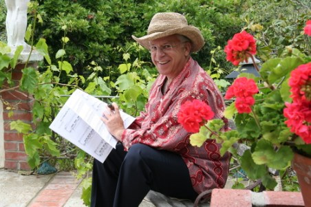 Pepe Romero sitting near bright red flowers reading a score