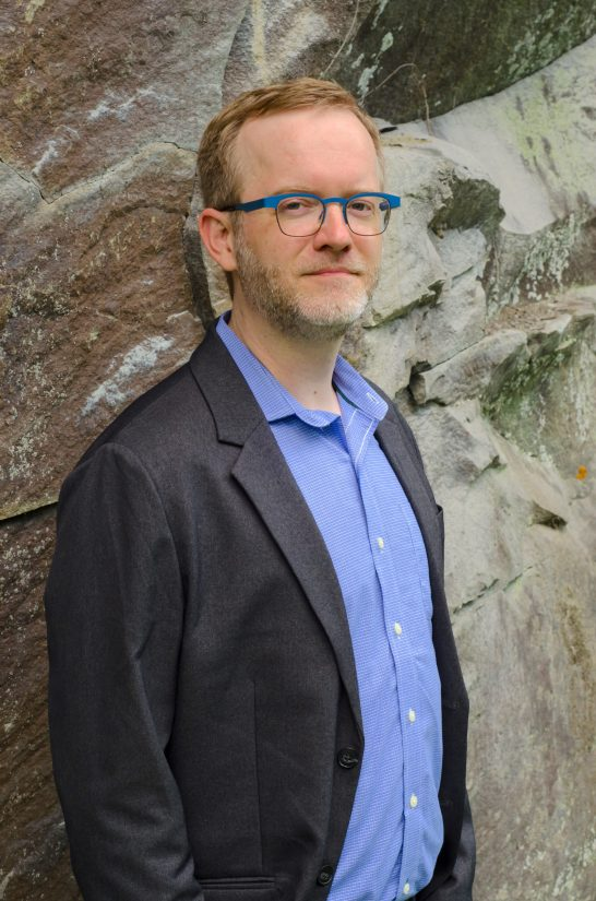 Jason Haaheim leaning against a stone wall, grey suit jacket and teal glasses.