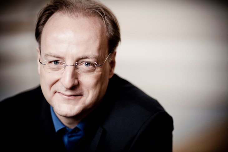 close up picture of Christoph-Mathias  Mueller wearing a black jacket and blue shirt.