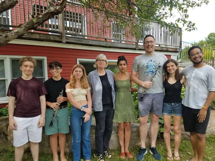 Andrew Parker posing at Kinhaven music school with current students, and teacher, Mary Watt.
