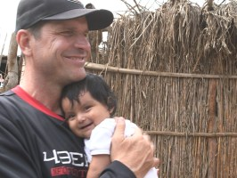Jim Harbaugh holds one of the locals' baby.