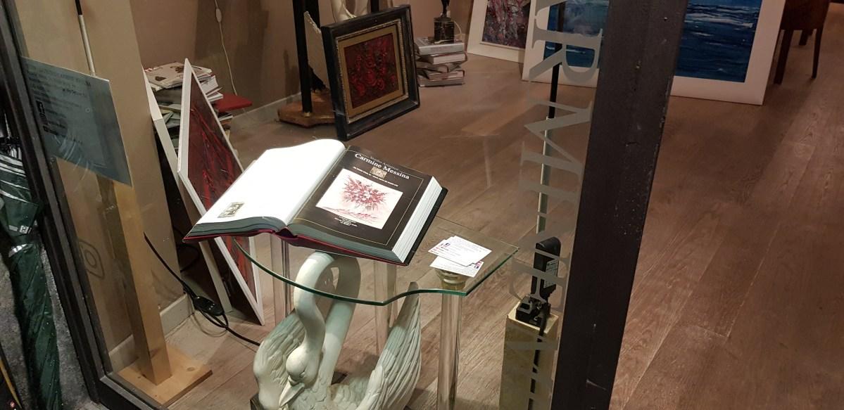 Nella vetrina dell'atelier il catalogo con la voce Carmine Messina, il pittore intervistato da ellie