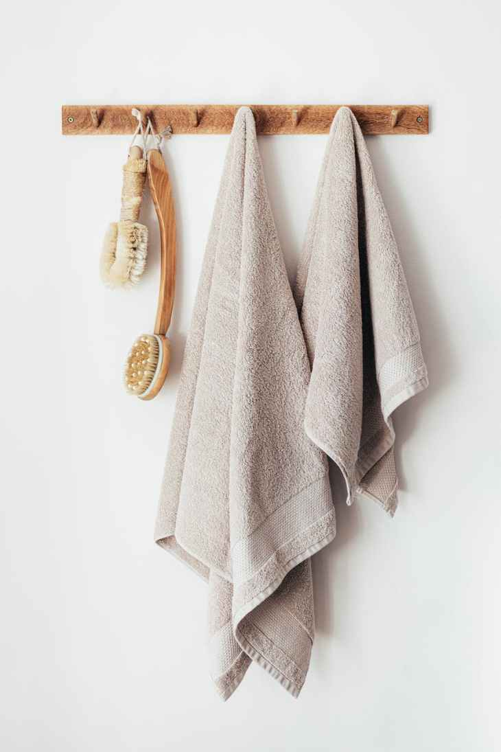wooden hanger with towels and body brushes