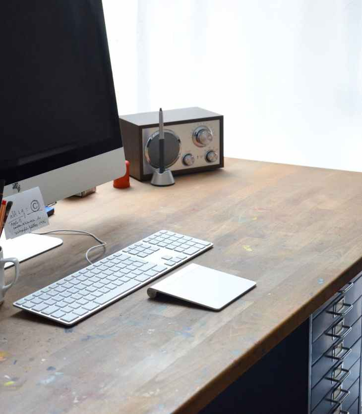 modern workplace with computer and portable radio on wooden table