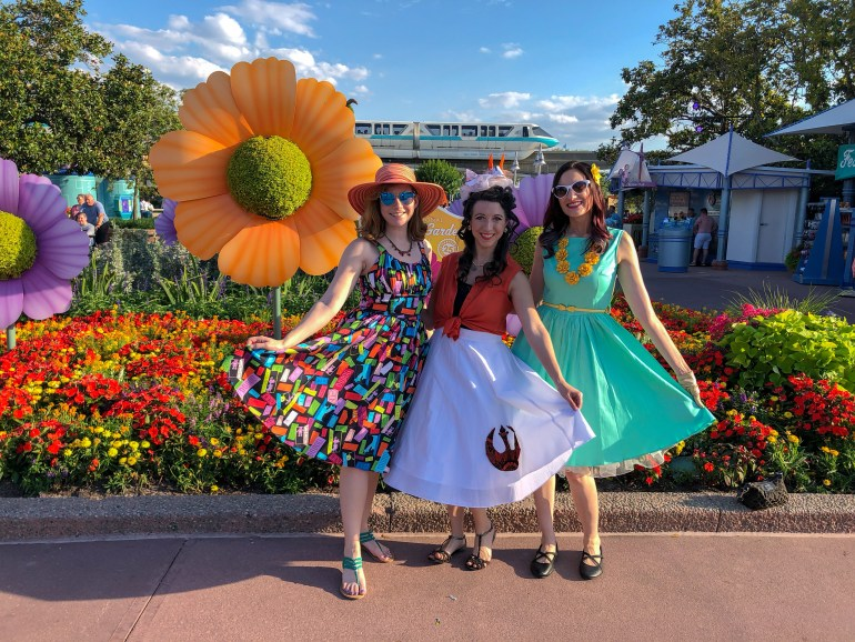 Theresa dressed up for Dapper Day with two friends, posing in front of a large orange flower display at Epcot's Flower and Garden Festival