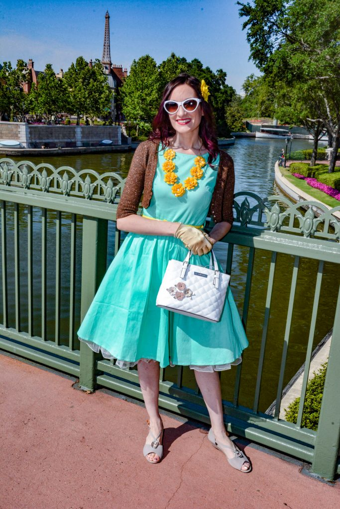 Theresa DisneyBounding as Clarice the Chipmunk, standing on a bridge in front of the France pavilion at Epcot with the Eiffel Tower in the background.