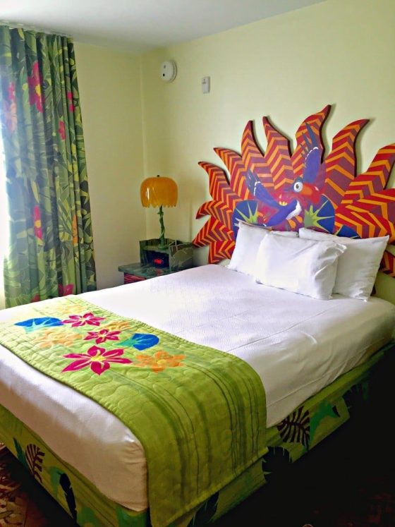 A bed with brightly colored linens and headboard featuring Zazu from The Lion King.