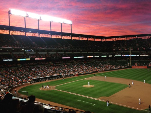 Sunset at an Orioles baseball game with an orange, pink and purple sky overlooking the field.