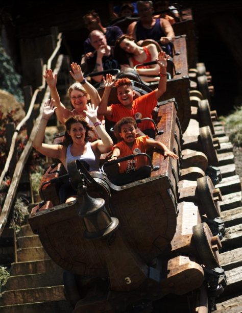 Theresa's family smiling with their hands in the air while riding Seven Dwarfs Mine Train