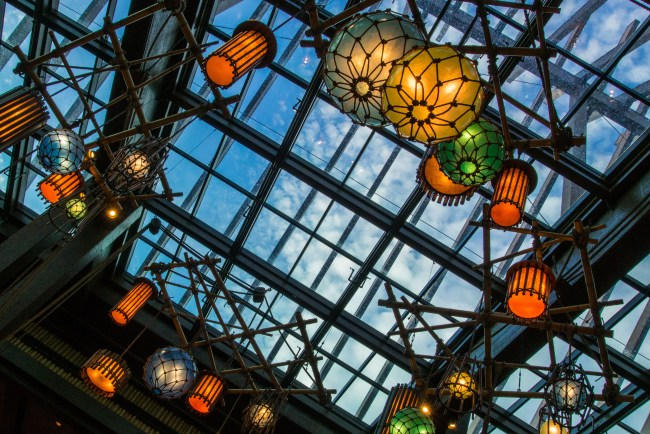 At Disney's Polynesian Resort, looking above the lobby you see blue skies and brightly colored light fixtures, making it one of the Best Walt Disney World Hotels