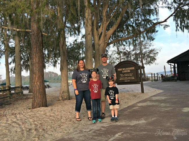 Family of four standing on the edge of the sidewalk leading towards a beachy area at Disney's Fort Wilderness resort.