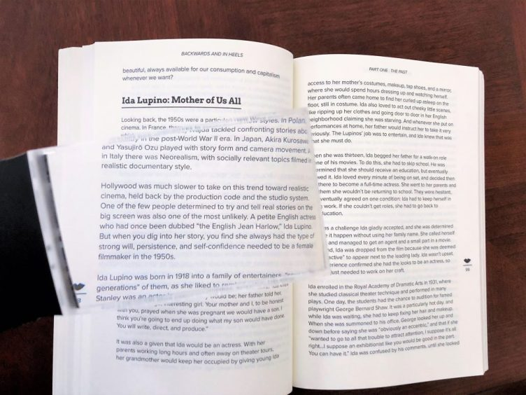 Magnifier held over open book to assist with understanding vision loss