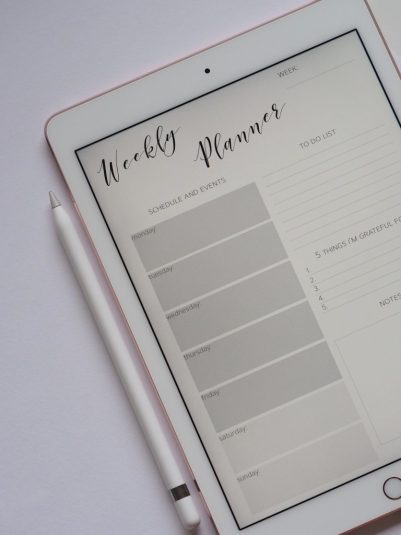 White tablet and pen, showing a weekly planner on the screen - perfect for scheduling events and a to do list for a year of opportunities!