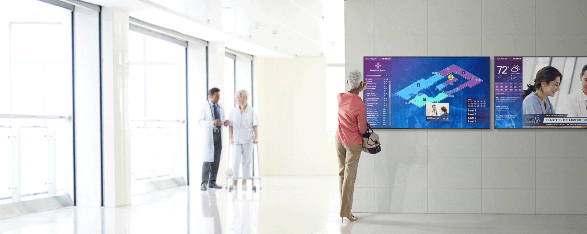 Woman uses digital signage to navigate a hospital.