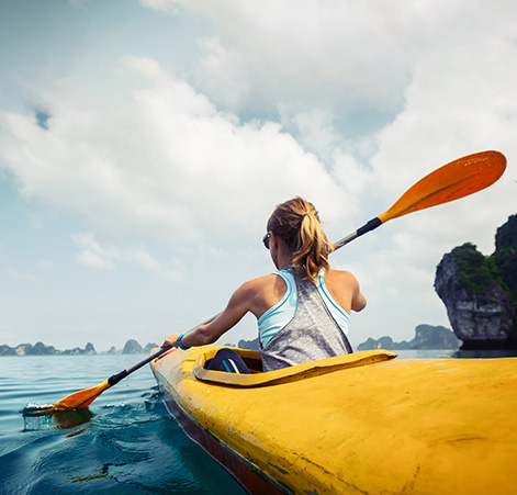 Image of a woman rowing a boat.