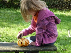 girl playing alone with a pumpkin