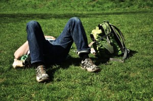 teen boy asleep in grass with backpack nearby