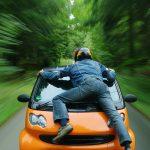 teen riding on hood of a car