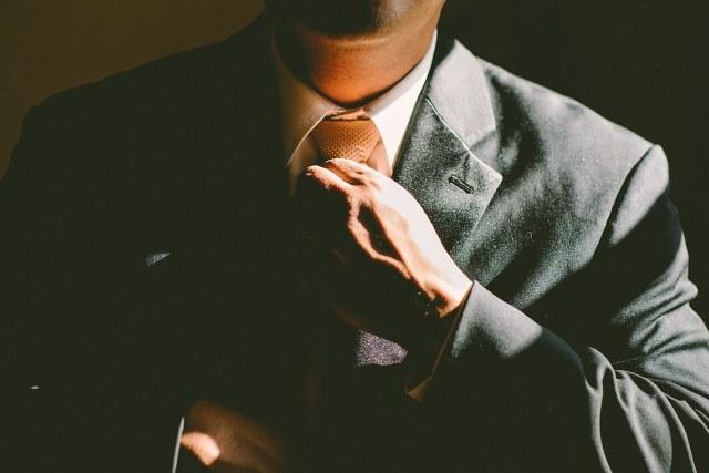 Muž, upravující si kravatu
